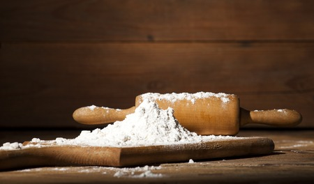 Ingredients and utensils for the preparation of bakery products - flour, rolling pin, board - on rustic wooden table. Front view and free text space.
