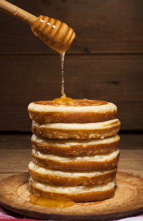 drizzler: A tall stack of pancakes with dripping honey from drizzler on wooden background.