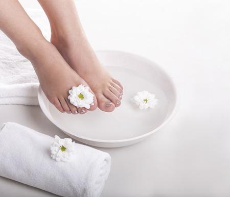 Weibliche Füße mit Spa-Schüssel, Handtücher und Blumen auf weißem Hintergrund