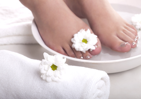 footcare: Female feet with spa bowl, towels and flowers on white background