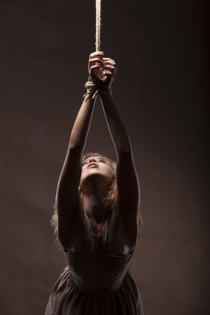Mooie jonge vrouw met een kabel rond de handen op donkere bruine achtergrond, studioschot.