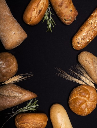 Assortment of baked goods on black table with free copy space for text. Top view. Stock Photo
