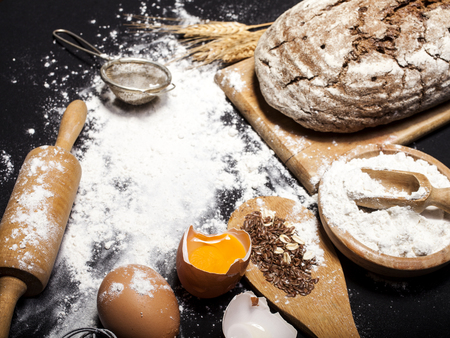 Ingredients and utensils for the preparation of bakery products - flour, eggs, rolling pin, whisk, strainer, bread - on black table with free copy space Banque d'images