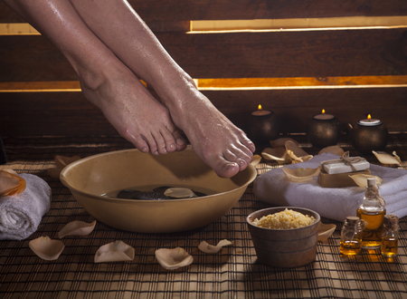 Female feet with drops of water, spa bowl, towels, flowers, candles, sea salt and bottles with essential oil. Foot spa concept. Stock Photo