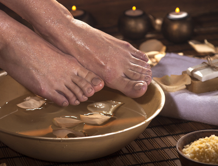 footcare: Female feet with drops of water, spa bowl, towels, flowers, candles, sea salt and bottles with essential oil. Foot spa concept. Stock Photo