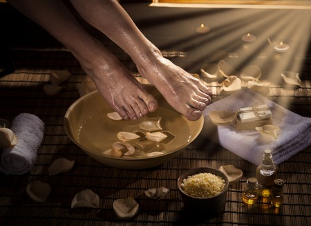 Female feet with drops of water, spa bowl, towels, flowers, candles, sea salt and bottle with essential oil. Special lighting effect. Foot spa concept.