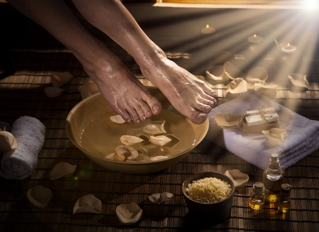 footcare: Female feet with drops of water, spa bowl, towels, flowers, candles, sea salt and bottle with essential oil. Special lighting effect. Foot spa concept.