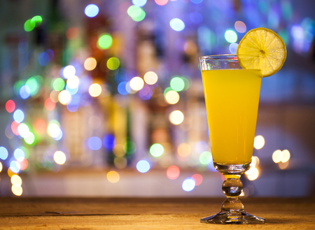 sweet vermouth: Glass of orange cocktail on a bar lights background. Stock Photo