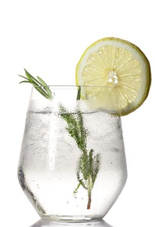 enebro: Vidrio con la bebida alcohólica con limón y hielo aislados sobre fondo blanco. Foto de archivo