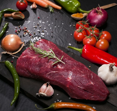 angus: Raw meat. Raw beef steak on a cutting board with herbs and vegetables.