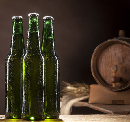 Close up of three glass bottles of beer and wooden barrel on wooden table and brown background