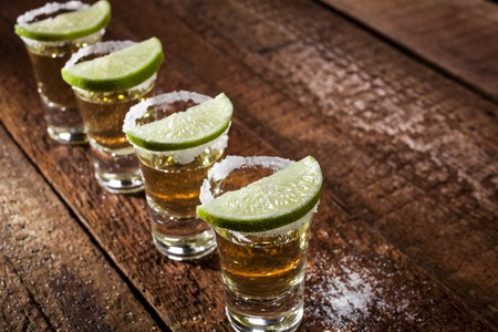 Gold tequila shots with lime fruits on wooden background