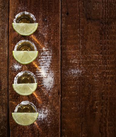 木製の背景に石灰フルーツ ・ ゴールド ・ テキーラ ショット