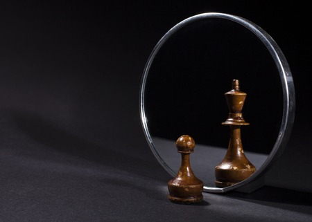 Pawn looking in the mirror and seeing a king. Black background. Stock Photo