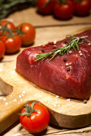 uncooked: Raw meat. Raw beef steak on a cutting board with herbs, spices and cherry tomatoes.