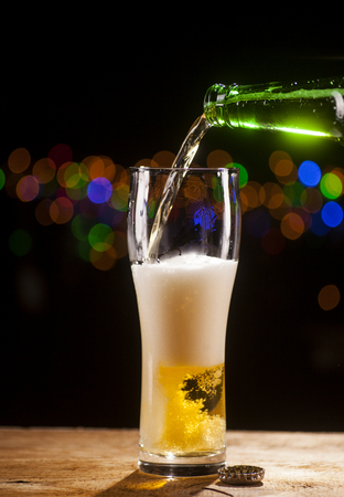 Beer is pouring into glass on wooden table and bar lights background. Banque d'images