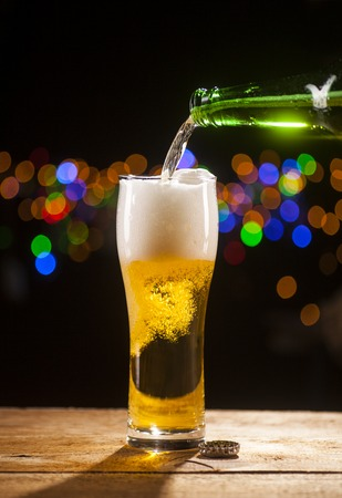 Beer is pouring into glass on wooden table and bar lights background. Stock Photo