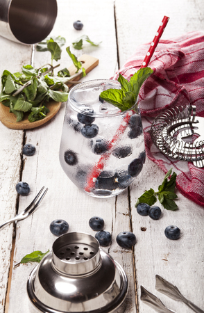 Summer cold drink with blueberry, mint and ice in glass on white wooden background