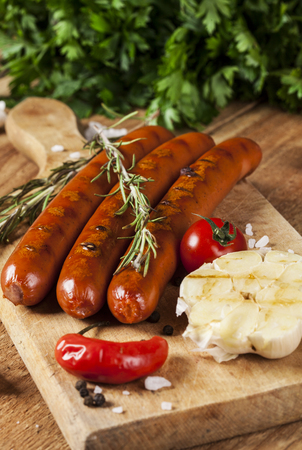 Wiener Sausages with vegetables on wooden background Stock Photo