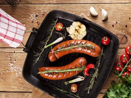 Salchichas a la parrilla con verduras y especias en una sartén sobre fondo de madera