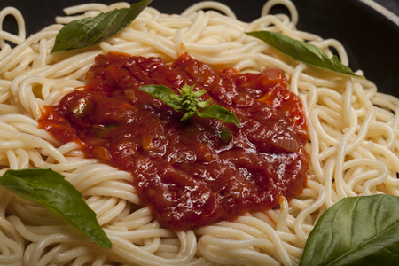 marinara sauce: Closeup of delicious spaghetti Bolognaise or Bolognese with savory minced beef and tomato sauce garnished with parmesan cheese and basil Stock Photo