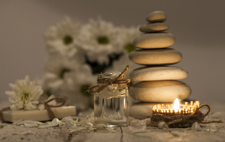 Chamomile essential oil, bouquet of chamomile flowers, stack of white rocks and candle Stock Photo