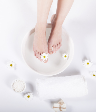 Female feet with spa bowl, towel and flowers on white background Stockfoto