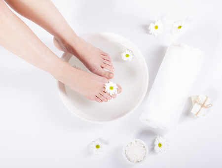 Female feet with spa bowl, towel and flowers on white background Stock Photo