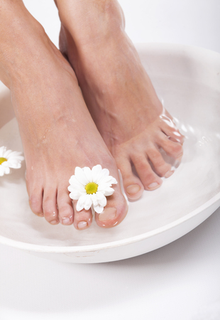 Female feet with spa bowl, towel and flowers on white background Фото со стока