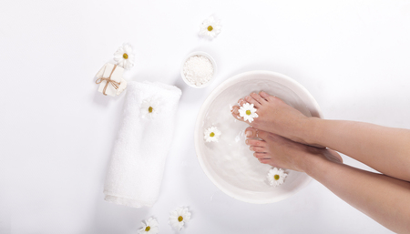 Female feet with spa bowl, towel and flowers on white background Фото со стока - 96703079