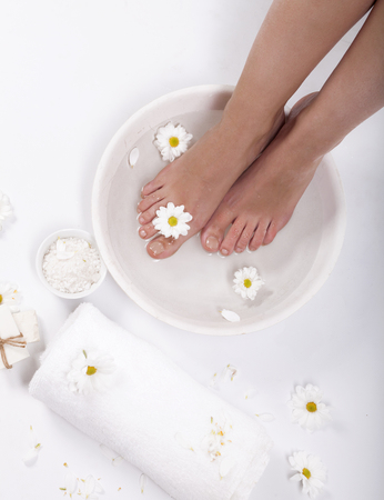 Female feet with spa bowl, towel and flowers on white background Banque d'images