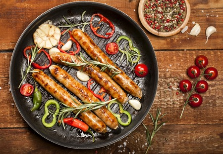 Fried sausages with spices, herbs and vegetables in a pan. On wooden background.