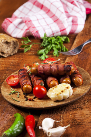 Festive cocktail sausages wrapped in crispy smoked bacon commonly known as 'Pigs in Blankets' on a wooden background Standard-Bild