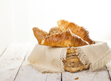 Croissants on a white wooden background with copy space