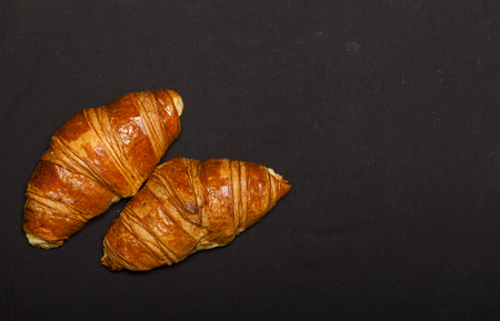 Croissants on black background with copy space