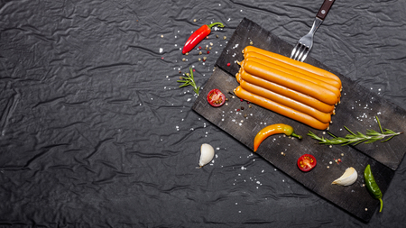 Wiener Sausages with spices on black background. Top view with copy space.