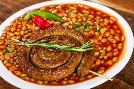 Beans with grilled spiral sausage, traditional european homemade meal Standard-Bild