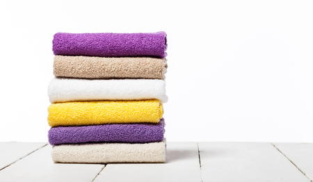 Stack of bath towels on light wooden table and white background closeup Banque d'images