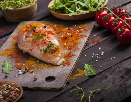 Board with raw chicken fillet with spices and fresh vegetables on a black background