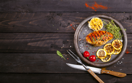 Grilled chicken fillet with fresh thyme, cherry tomato, lemon, garlic and spices in a slate plate on a black background