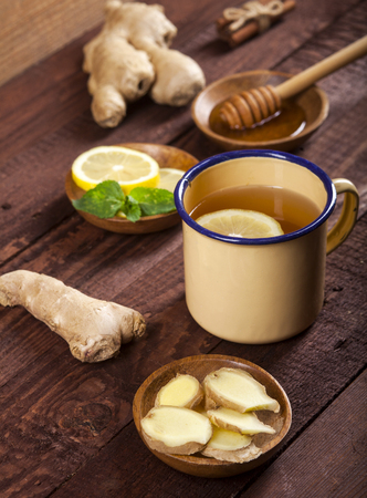 Ginger tea with lemon honey and mint on wooden background