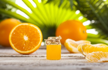 Bottle of essential oil from oranges on wooden table and green leaves background - alternative medicine Banque d'images