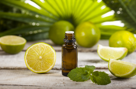 Bottle of essential oil from limes on wooden table and green leaves background - alternative medicine Imagens