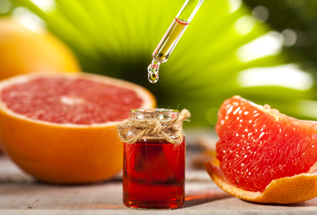 Bottle of essential oil from grapefruits on wooden table and green leaves background - alternative medicine