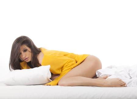 Young beautiful brunette woman with yellow pullover sitting in a bed on white background