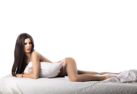 Joven hermosa mujer morena con un cuerpo perfecto en ropa interior de algodón blanco acostado en una cama sobre fondo blanco. Foto de archivo