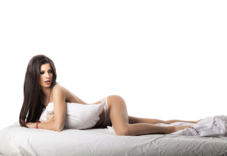 Young beautiful brunette woman with perfect body in white cotton underwear lying in a bed on white background