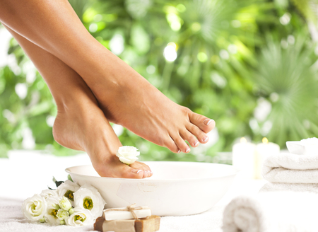 Female feet with spa bowl, towel, soap and flowers on white floor and tropical green leaves