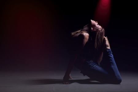 Young beautiful dancer in blue jeans posing on a dark studio background with red lights