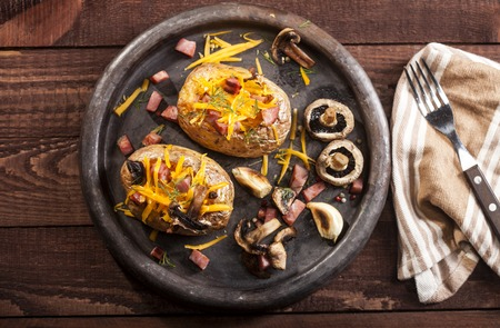 Baked stuffed potatoes with bacon, cheddar, mushrooms and dill on wooden table Foto de archivo
